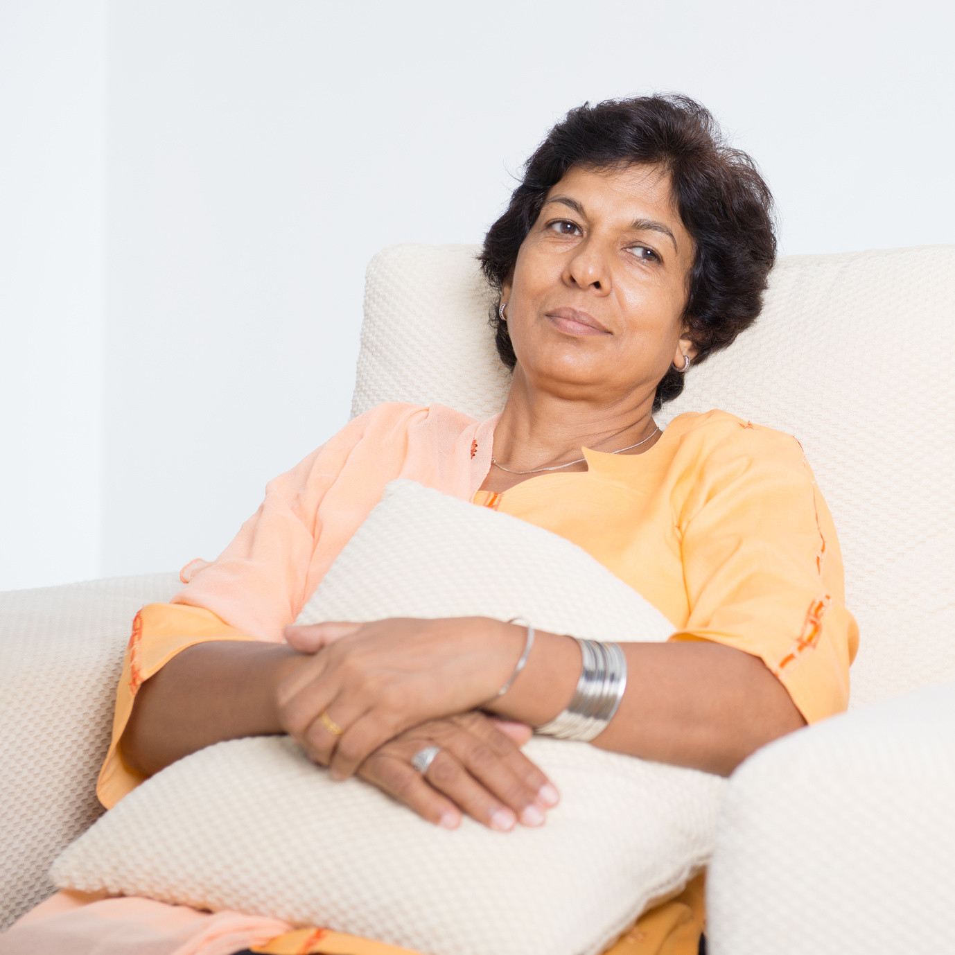 Portrait of a tired 50s Indian mature woman resting on sofa at home. Indoor senior people living lifestyle.
